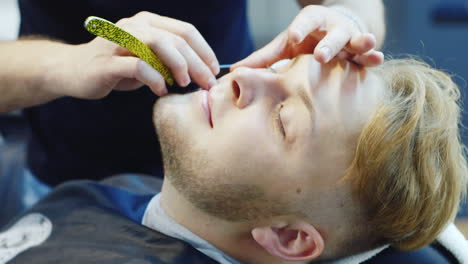 A-Young-Man-Is-Shaved-With-A-Dangerous-Razor-In-Barbershop-Hd-Video