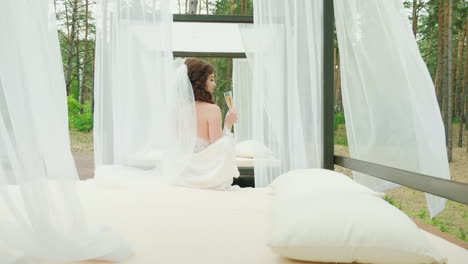 The-Bride-With-A-Glass-Of-Champagne-Sits-On-A-Lounger-Beside-The-Pool-Hd-Video