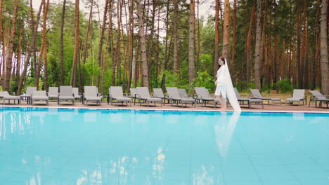 The-Bride-With-A-Long-Veil-Is-Walking-Around-The-Pool-Wedding-In-A-Luxury-Hotel-Slow-Motion-Video