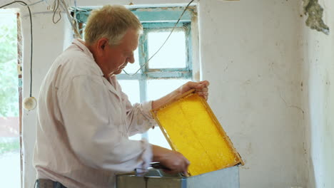 An-Elderly-Beekeeper-Works-With-Frames-For-Honey-Manual-Labor-In-The-Apiary-4k-Video