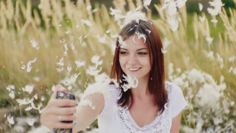 A-Woman-Makes-Selfie-On-A-Creative-Photo-Shoot-Everything-Is-Strewn-With-Feathers-Slow-Motion-Video