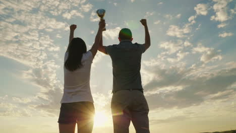 A-Man-And-A-Woman-Raise-Their-Hands-With-The-Champion-s-Cup-Victory-And-Success-Slow-Motion-Video