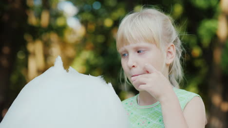 Portrait-Of-A-Fair-Haired-Girl-Eating-Sweet-Cotton-Wool-In-The-Park-A-Clear-Summer-Day-A-Happy-Vacat