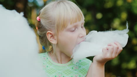 Cool-Blonde-Girl-6-Years-Old-Is-Eating-Sweet-Cotton-Wool-In-The-Park-Portrait-With-Shallow-Depth-Of-