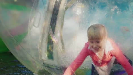 Fun-On-The-Water-A-Cheerful-Little-Girl-Plays-Inside-A-Transparent-Ball-In-The-Pool-4k-Slow-Motion-V