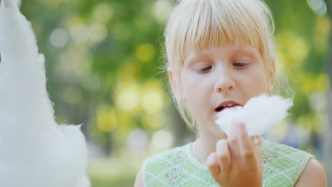 The-Girl-Is-Eating-Delicious-Sweet-Cotton-Wool-In-The-Park-Licks-His-Fingers-Out-4k-Video