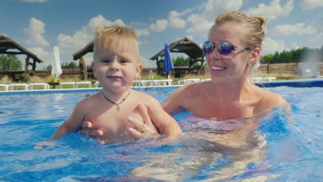 Mom-And-The-Baby-Boy-Swim-In-The-Pool-Have-Fun-Together