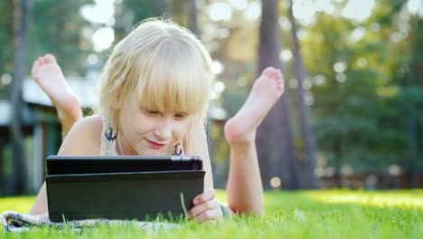 Blonde-Girl-6-Years-Playing-On-The-Tablet-Emotionally-Reacts-Lying-On-The-Lawn-In-The-Backyard-Of-Th