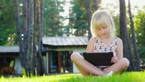 The-Girl-Is-Playing-On-The-Tablet-The-Sun-Beautifully-Highlights-Her-Blond-Hair-Sits-On-The-Lawn-Nea
