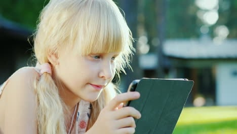 Portrait-Of-A-6-Year-Old-Girl-Playing-On-A-Tablet-Lies-On-The-Grass-Near-The-House-4k-10-Bit-Video