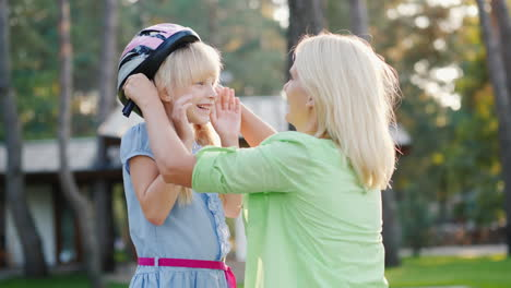 Mom-Puts-On-A-Protective-Helmet-For-Her-Daughter-Concept---Care-And-Safety-4k-Video