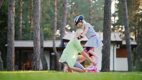 Happy-Childhood-A-Young-Mother-Helps-To-Put-Roller-Skates-On-Her-Daughter-In-The-Backyard-Of-Their-H