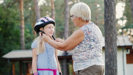 Senior-Woman-Puts-On-A-Protective-Helmet-For-Her-Daughter-Concept---Care-And-Safety-4k-Video