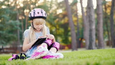The-Girl-Is-Sitting-Near-The-House-Enjoying-The-Tablet-Rolled-On-Roller-Skates---On-Her-Helmet-And-R