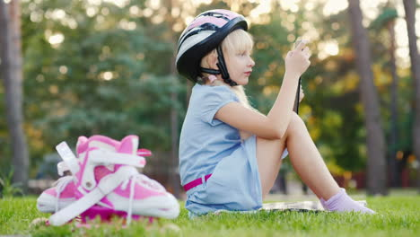 A-Girl-In-A-Protective-Helmet-Is-Playing-On-A-Tablet-Next-To-Her-Are-Roller-Skates-Hd-Video