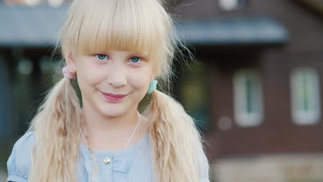 Portrait-Of-A-Blond-Girl-6-Years-Old-Smiling-At-The-Camera-It-Stands-In-The-Background-Of-His-House-