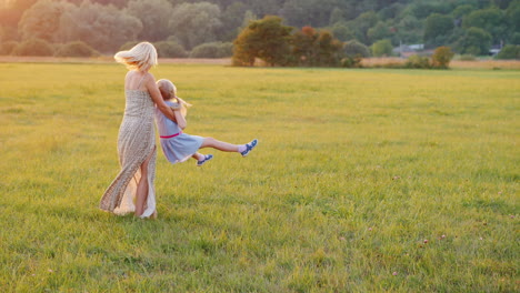 Mom-Plays-With-Her-Daughter-Twists-Her-Around-Her-On-A-Beautiful-Meadow-At-Sunset-Active-Lifestyle-4