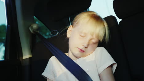 The-Girl-Is-6-Years-Old-Riding-In-The-Back-Seat-Of-The-Car-Buckled-With-A-Seat-Belt-And-Sleeps-On-Th