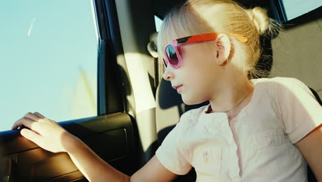 A-6-Year-Old-Girl-In-Sun-Protective-Pink-Glasses-Is-Riding-In-The-Back-Seat-Of-The-Car-It-Is-Fastene