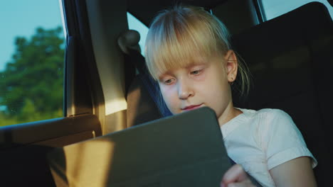 Caucasian-Girl-6-Years-Riding-In-The-Back-Seat-Of-The-Car-Playing-On-The-Tablet-Traveling-With-A-Chi