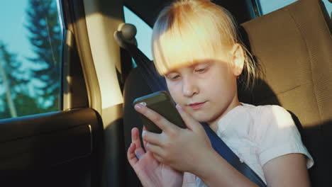 The-Girl-Is-Traveling-In-A-Car-Playing-On-A-Smartphone-On-The-Road-With-A-Child-4k-Video