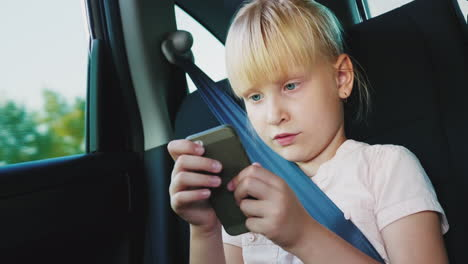 Technology-On-The-Road-The-Girl-Is-6-Years-Old-Playing-On-A-Smartphone-She-Is-Riding-A-Car-Seat-4k-V