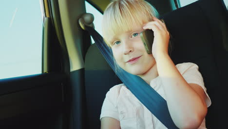 Funny-Girl-6-Years-Old-Speaks-On-The-Phone-Rides-In-The-Back-Seat-Of-The-Car-It-Is-Fastened-With-A-S