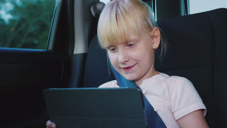 Fun-On-The-Road-The-Girl-Uses-A-Tablet-Rides-In-The-Back-Seat-Of-The-Car-4k-Video