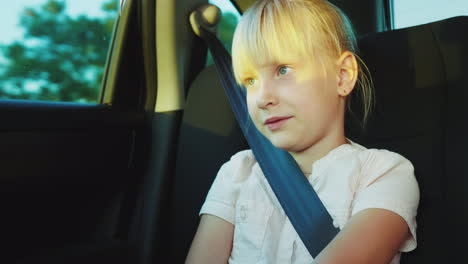 A-Blonde-Girl-Of-6-Years-Enjoys-A-Trip-In-The-Car-Sits-In-The-Back-Seat-Fastened-With-A-Seatbelt-4k-