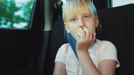 Snack-On-The-Road-The-Girl-Eats-An-Apple-Rides-In-The-Back-Seat-Of-The-Car-4k-Video