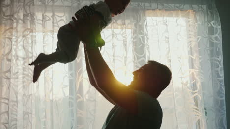 Silhouettes-Of-Loving-Parents-With-A-Child-At-The-Window-Of-Their-Apartment
