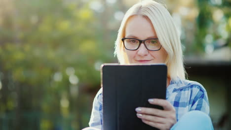 Portrait-Of-A-Young-Woman-Enjoying-A-Tablet-In-The-Courtyard-Of-Her-Home-Concept---Technology-And-Di