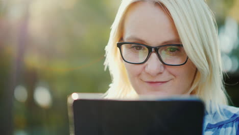 Portrait-Of-A-Young-Woman-Wearing-Glasses-Enjoying-A-Tablet-In-The-Park-Beautiful-Sun-Glare-4k-Slow-
