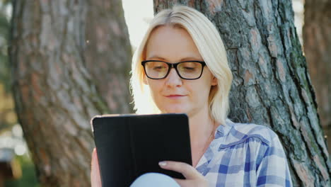 Attractive-Young-Woman-In-Glasses-Uses-A-Tablet-Sits-In-A-Park-Near-A-Tree-Beautiful-Light-Before-Su