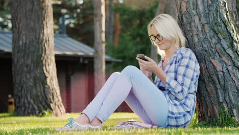 A-Young-Woman-Is-Using-A-Smartphone-Sits-On-The-Grass-Under-A-Tree-In-The-Backyard-Of-The-House-4k-V