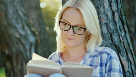 A-Blonde-Young-Woman-In-Glasses-Reads-A-Book-In-The-Park-Sits-Near-A-Tree-Beautiful-Light-Before-Sun