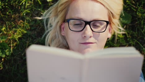 Portrait-Of-A-Young-Woman-In-Glasses-Lying-On-A-Lawn-In-The-Park-And-Reading-A-Book-4k-Video