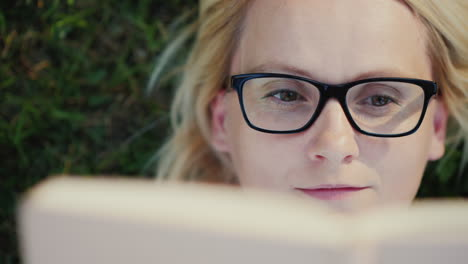 Portrait-Of-A-Young-Woman-In-Glasses-Lying-On-A-Lawn-In-The-Park-And-Reading-A-Book-Close-Up-4k-Vide