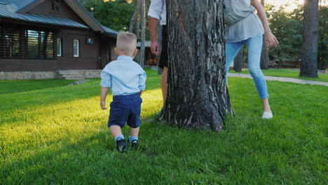 Happy-Parents-Play-Hide-And-Seek-With-A-Baby-Boy-He-Runs-Happily-Behind-Them-Around-The-Tree-Happy-T