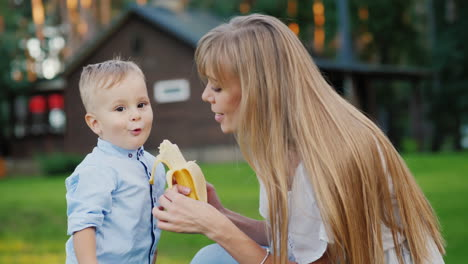 Young-Mother-Feeding-A-Kid-With-A-Banana-4k-Video