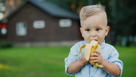 Cheerful-1-Year-Old-Baby-Is-Eating-A-Banana-It-s-Standing-On-The-Back-Of-The-House-4k-Video