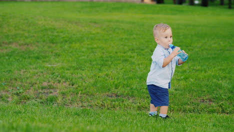 Funny-Kid-1-Year-Is-Drinking-Water-From-A-Bottle-It-Stands-On-A-Green-Lawn-Coolly-Staggers-Fun-Video
