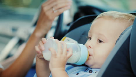 Baby-1-Year-Old-Drink-Milk-From-A-Bottle-Sits-In-A-Child-Car-Seat-4k-Video