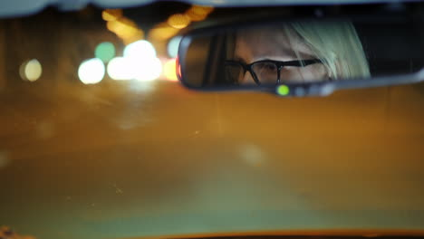 A-Woman-In-Glasses-Drive-A-Car-Through-The-Night-City-Her-Face-Is-Reflected-In-The-Rearview-Mirror-4