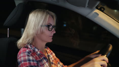 A-Woman-In-Glasses-Drives-A-Car-Through-The-Night-City-4k-Video