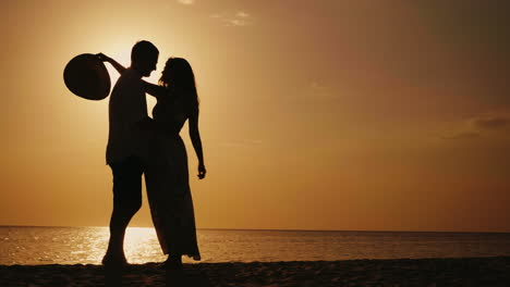 Silhouette-Of-Couple-In-Love-They-Look-At-Each-Other-Hug-And-Kiss-At-Sunset-Against-The-Background-O