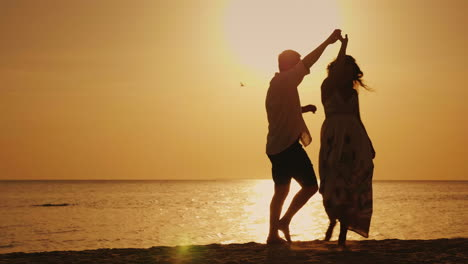 Silhouettes-Of-A-Young-Couple-Cool-Dancing-Against-The-Backdrop-Of-The-Sea-And-The-Setting-Sun-Merry