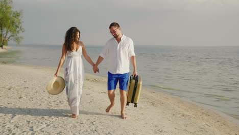 A-Loving-Couple-Is-Walking-Along-A-Tropical-Beach-Carry-A-Travel-Bag-Steadicam-Shot