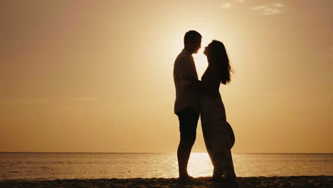 Romantic-Young-Couple-Kissing-At-Sunset-Against-The-Sea-4k-Slow-Motion-Video