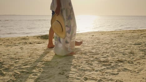 A-Young-Couple-Is-Walking-Barefoot-On-The-Sand-On-The-Beach-In-The-Frame-Only-The-Legs-Are-Visible-V